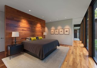In the master bedroom, a wooden accent wall with coat hooks on one side serves as a partition for the bed.