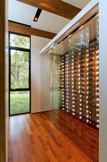 A glass-encased wine storage system lets the owners to select specific bottles with ease.