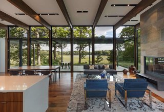 The house is sited on a wooded plateau overlooking a wetland and lake beyond.