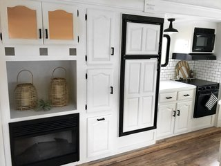 The kitchen has a fireplace, oven, microwave, electric cooktop, and plenty of discreet storage.