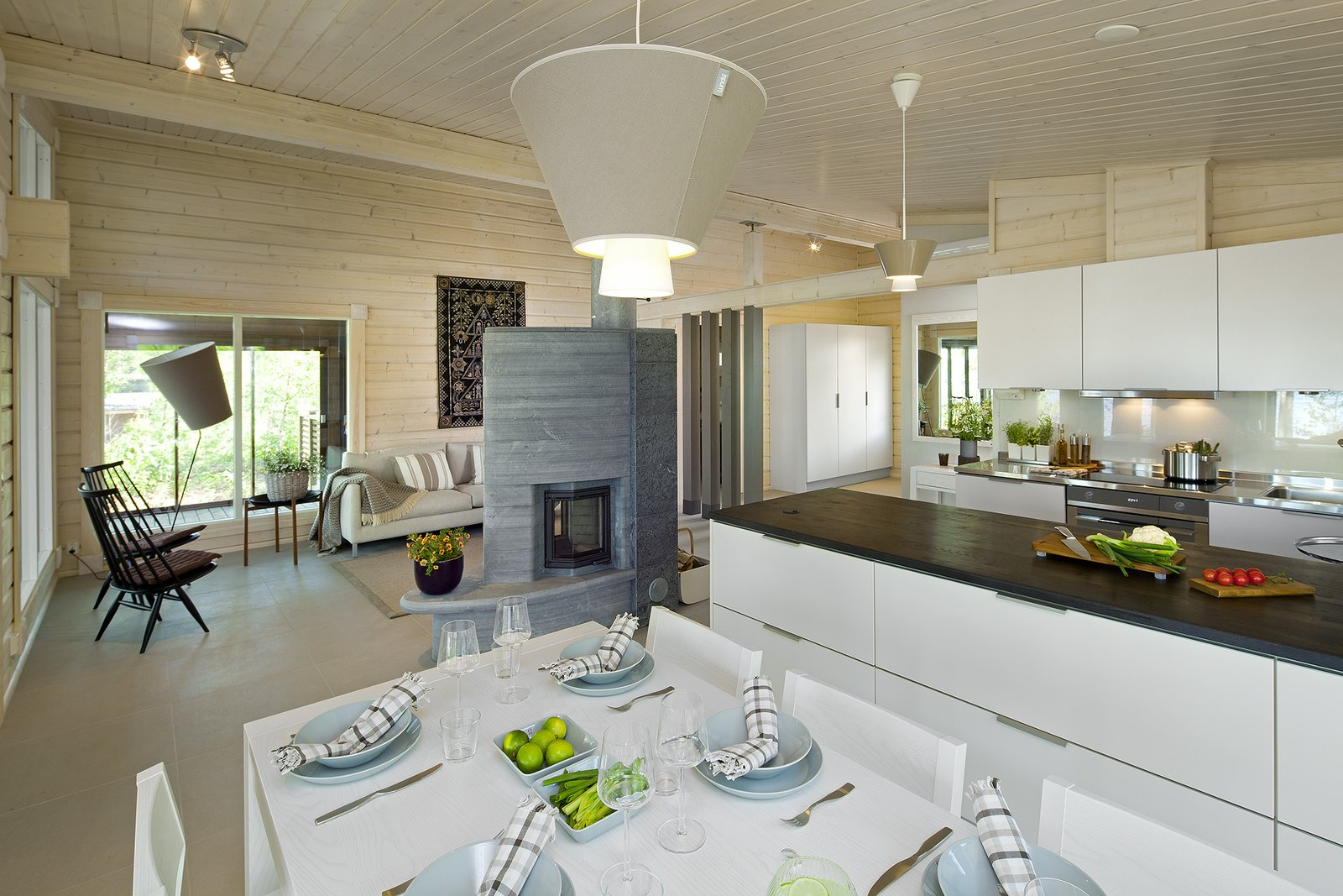 Dining Room, Pendant Lighting, Wood Burning Fireplace, Table, Chair, and Ceiling Lighting This model has vaulted ceilings and an glass-encased outdoor area with a large overhanging roof.  Photo 11 of 21 in These 8 Log Cabin Kit Homes Celebrate Nordic Minimalism