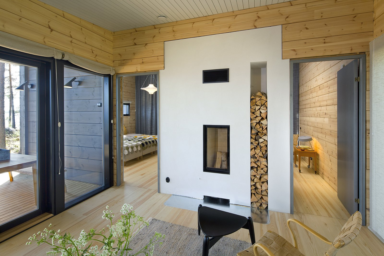 The simple interior decor, and natural materials like wood and stone help this holiday home harmonize with its environment.  Photo 13 of 21 in These 8 Log Cabin Kit Homes Celebrate Nordic Minimalism