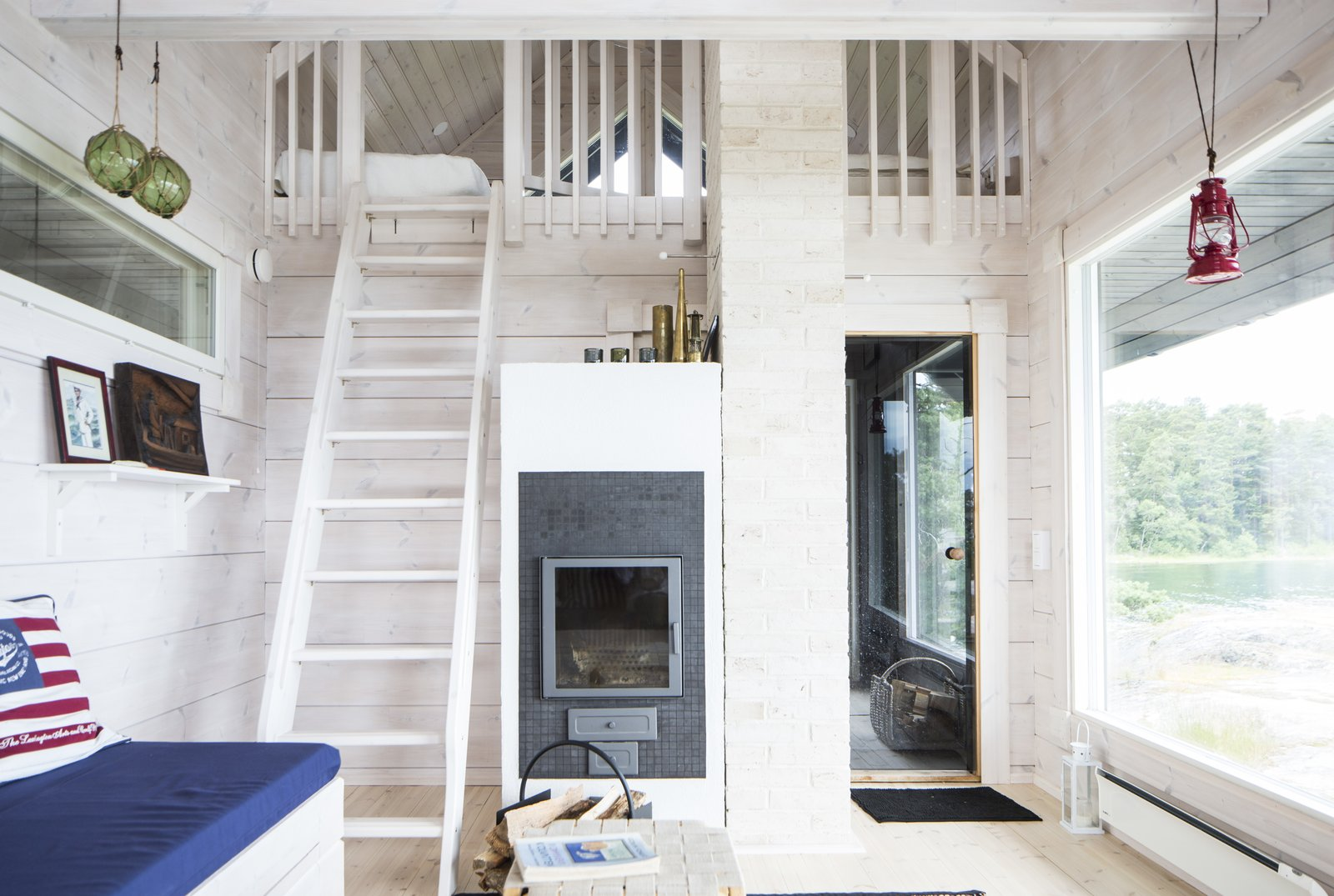 The interiors are furnished in light colors that reflect the sunlight streaming in through the large windows.  Photo 15 of 21 in These 8 Log Cabin Kit Homes Celebrate Nordic Minimalism