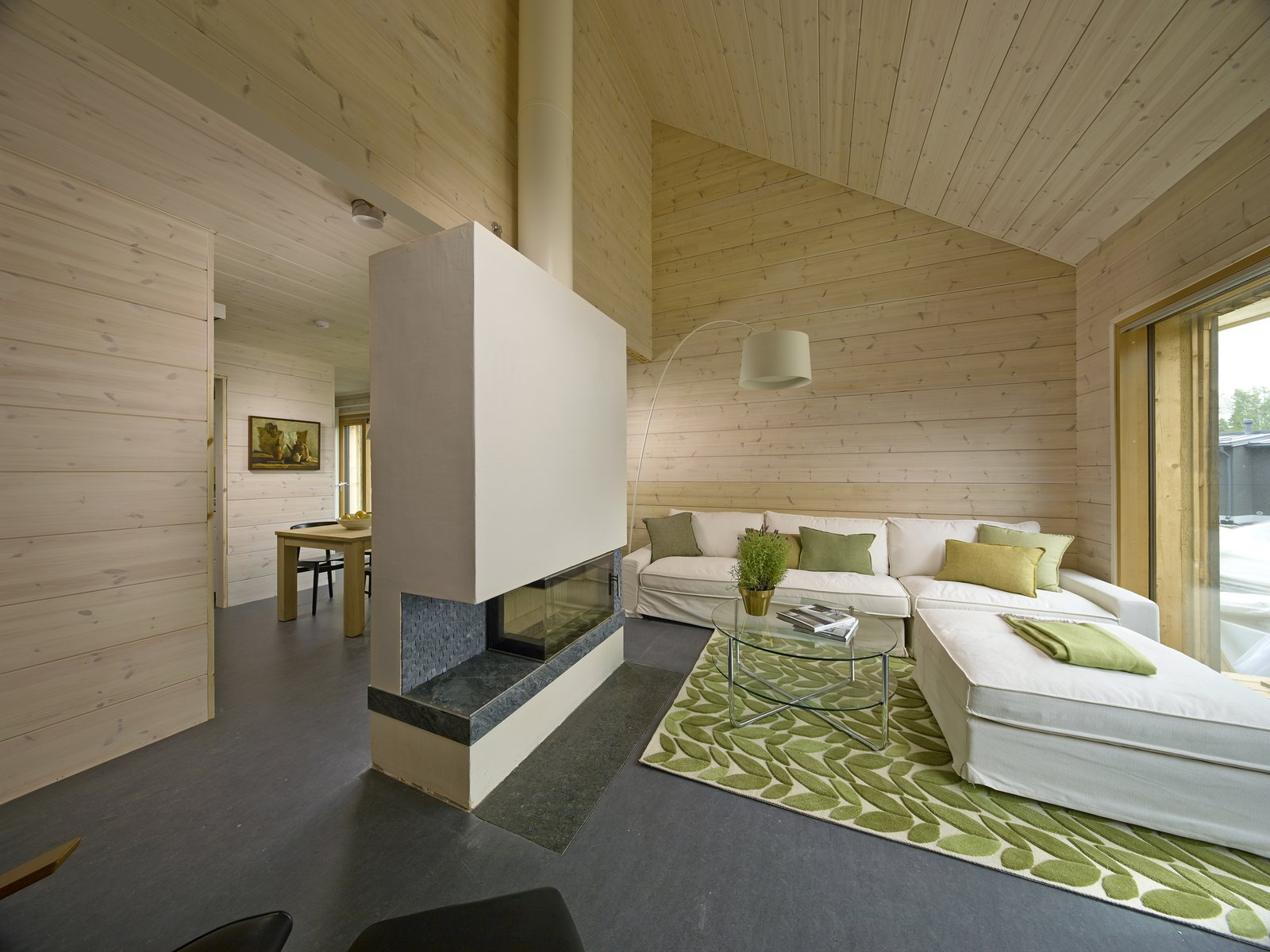 Living Room, Ribbon Fireplace, Floor Lighting, Coffee Tables, Ottomans, Sofa, Lamps, and Rug Floor A Honka Fusion log house is split into two separate living units with a shared entrance, Savukvartsi is energy efficient with very small carbon footprint.  Photo 17 of 21 in These 8 Log Cabin Kit Homes Celebrate Nordic Minimalism