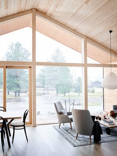 The kitchen and living areas are located at the front, where the glazed façade allows more light penetration, while the bedrooms, bathroom, and sauna are located at in the back of the house.