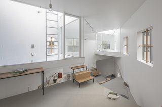 13 Spiraling Platforms Increase Space and Connection in This One-Room Home - Photo 7 of 13 - A study area is illuminated by windows on three sides.