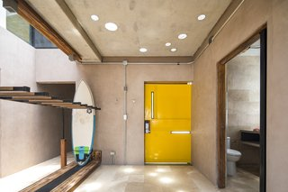 The bright yellow door adds a playful touch to a concrete abode. There is ample storage for surf gear throughout the dwelling, creating a connection between inside and out.