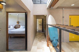 A Concrete Abode Becomes a Surfer's Paradise - Photo 11 of 23 - A bedroom with two beds is located in one of the buildings.