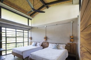 Floor-to-ceiling glass windows help to bring the green outdoors into the bedroom.