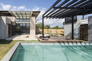 A Concrete Abode Becomes a Surfer's Paradise - Photo 6 of 23 - The layout of the three buildings creates a private garden space within the site. One building houses the bedrooms, while the other two feature several social zones.