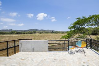 Because the house is sited on a former rice plantation near Playa Guiones, the surrounding flat geography allows for the exterior landscapes to be framed seamlessly from the interior.