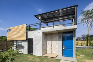 A smaller rectangular building between the two blocks is used as a pool house, as well as a storage area for surfing gear. The roof deck features a pergola-shaded plunge pool.