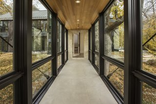 Simplistic recessed modern farmhouse lighting provides just the right touch of illumination in this open corridor, allowing the owner to  enjoy the autumn foliage outdoors.