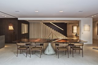 The color and sculptural form of the dining table also complements the art on the walls.