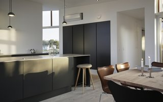 Rent This Danish A-Frame For Your Next Nordic Escape - Photo 4 of 11 - A peek at the dark, streamlined kitchen in the open-plan living area.