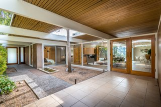 The living room feeds into a courtyard with a water feature.