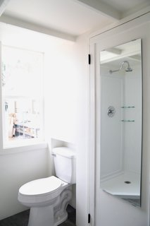 The bathroom fits a shower, vanity with roll out drawers, porcelain toilet, and hookups for a washer/dryer combination unit, as well as storage.