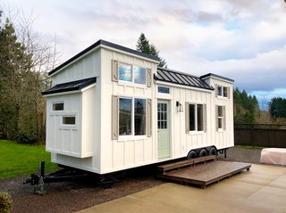 The tiny home rests upon a 28' x 8.5' Iron Eagle Tiny House Trailer with three 7K axles, trailer brakes, and road lighting. It has board and batten siding with Pacific Cedar accents,  a standing seam metal roof, and a glass exterior door.