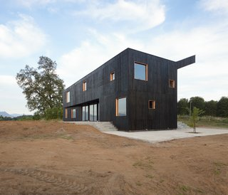 The house's dark façade, clad in vertically oriented, stained softwood timber slats, resembles the black volcanic stone structures that are commonly seen in the region.