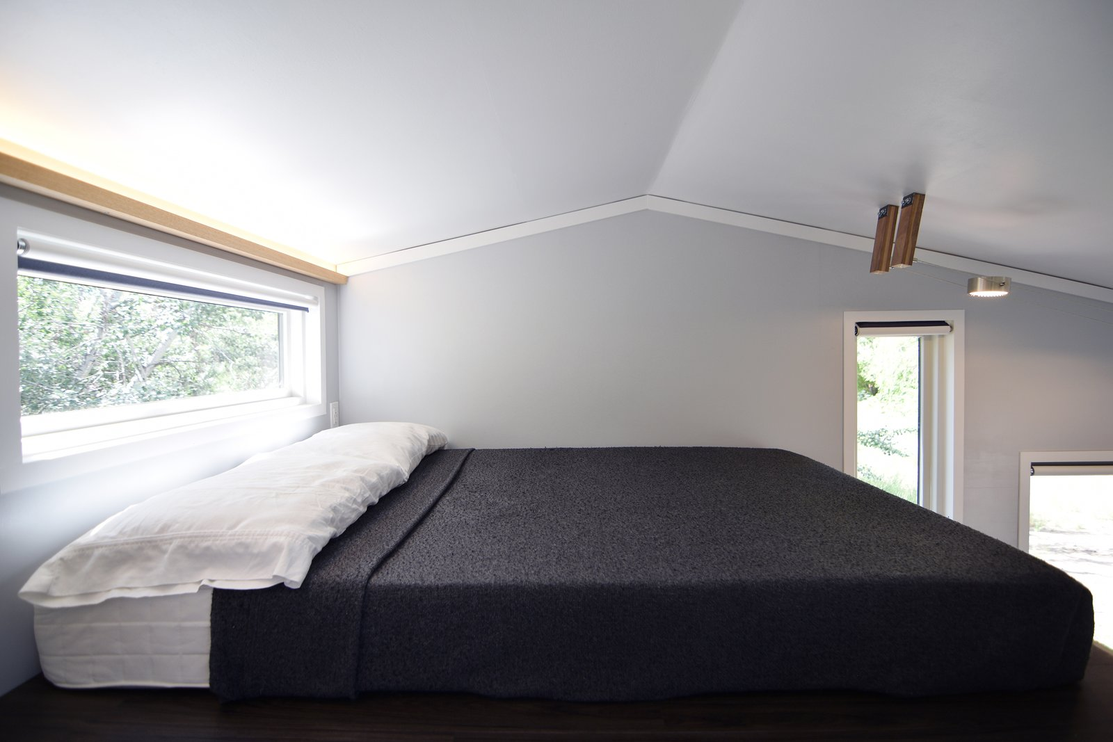 Up in the loft, a full size mattress is set parallel to the length of the house, with a strip of window gently illuminating this rest area.