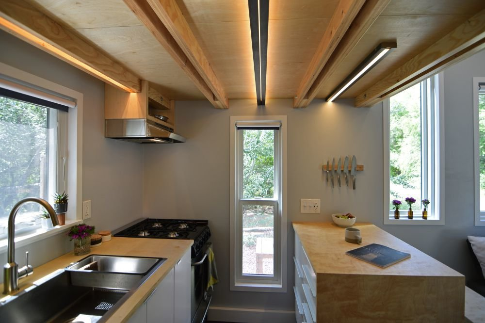 The galley-style kitchen is located below the sleeping loft, and has identical operable windows on each side to bring in an abundance of light and cross breezes, while opening up the interiors to views in both directions.