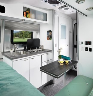 The trailer's fiberglass structure was styled by automotive designer Bryan Thompson, who had previously worked on Airstream's Basecamp model. The semi-monocoque fiberglass structure features an expansive, low-stance windshield.