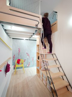 On the main level, the designers created an alcove playroom for the children. This area doubles as storage space for the kid's toys, so the main living area can remain clutter-free. From the alcove playroom, a ladder leads up to a mezzanine loft with a double-bed and two single beds.