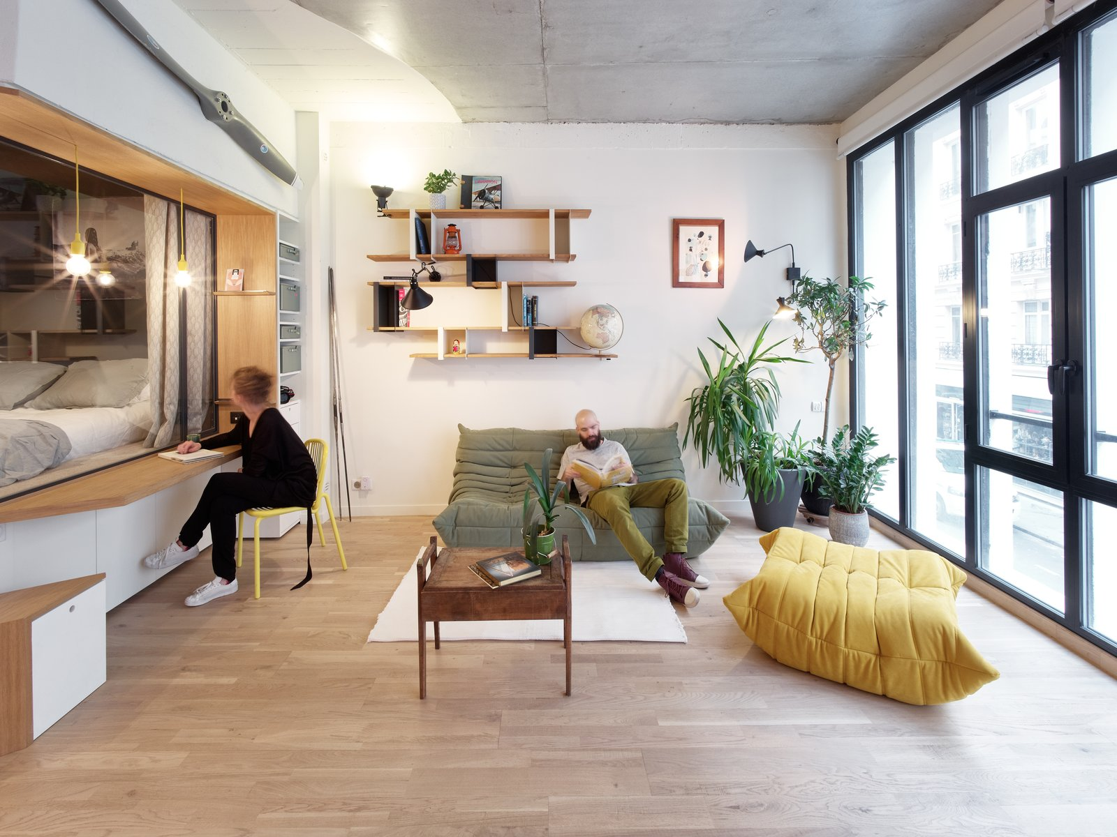 Living, Sofa, Lamps, Desk, Shelves, Light Hardwood, Chair, Coffee Tables, Rug, Pendant, and Wall  Best Living Desk Shelves Photos from This Compact Home in Paris Has Nearly 70 Concealed Closets