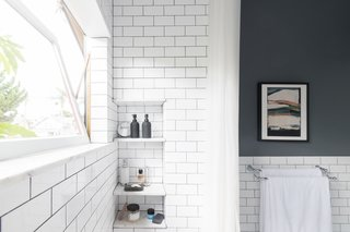 """For the bathroom, we kept the only original elements that remained after the space was remodeled in the 1980s, then added period-style tiles, plumbing, along with new storage, and a custom window,"" she says."