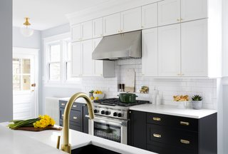 A classic subway tile backsplash with contrasting grey grout and stacked cabinets with matte brass hardware and fixtures emphasize the classic feel of the home. The new cabinets include pull-out pot and pan drawers, a waste and recycling compartment, pantry roll-outs, a spice pull-out, and base tray storage.