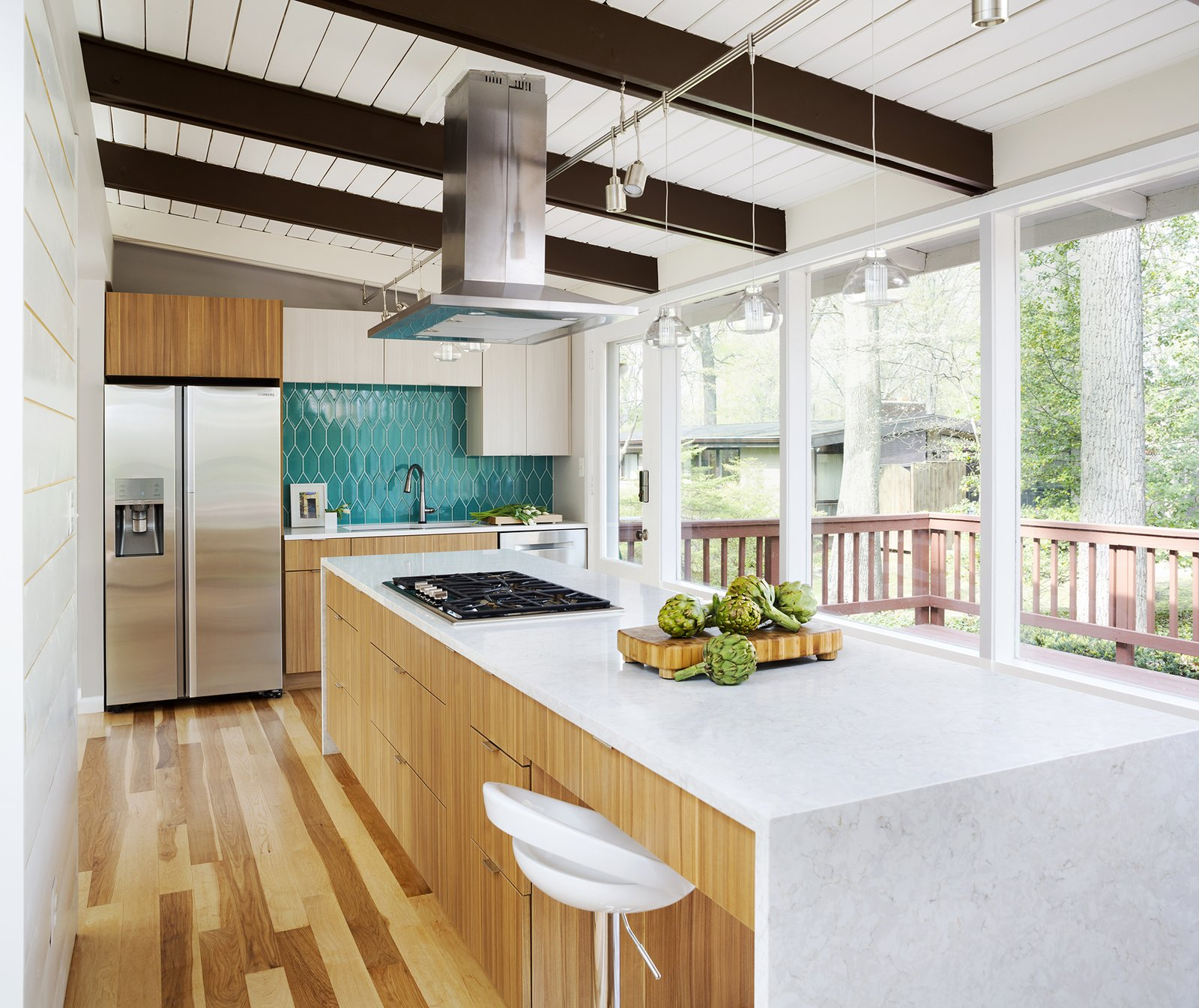 Kitchen, Porcelain Tile Backsplashe, Wood Cabinet, Engineered Quartz Counter, Light Hardwood Floor, Refrigerator, Track Lighting, Cooktops, Dishwasher, Range Hood, Undermount Sink, and Pendant Lighting Ceaserstone in Blizzard was used for the perimeter countertop, and Silestone in Lusso for the island top and the waterfall edges.  Photo 8 of 13 in Before & After: Two Masterful Kitchen Renovations by Case Design
