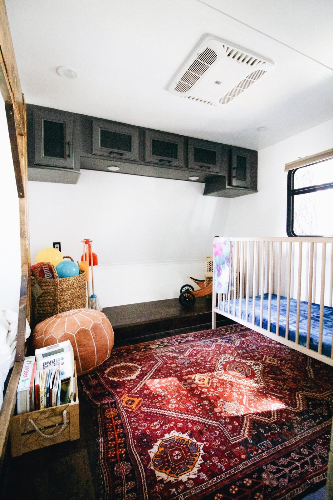 The children's room has a sliding closet and dresser, a short mattress and a tiny entertainment zone.
