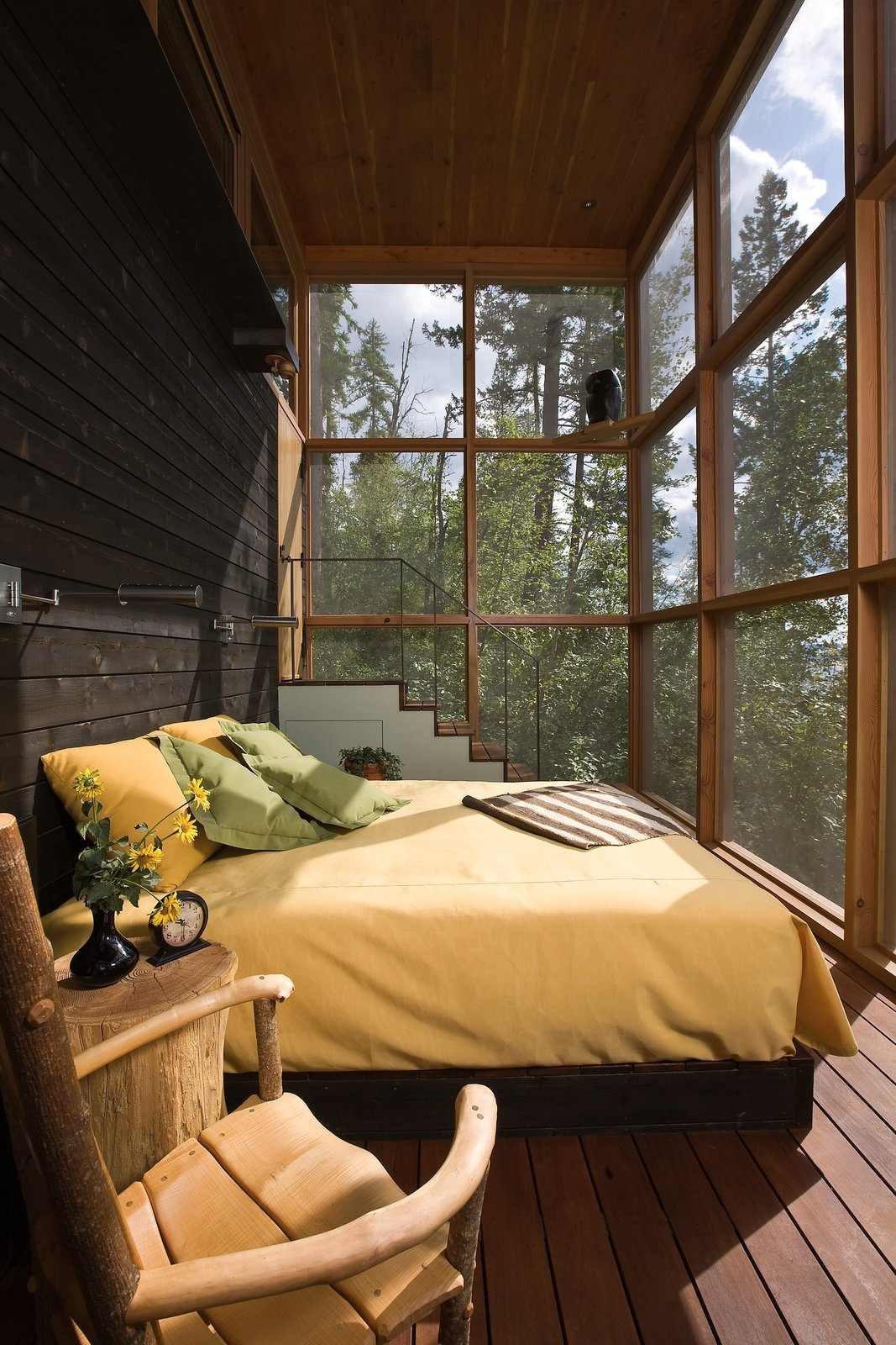 Bedroom, Medium Hardwood Floor, Chair, Bed, and Night Stands A screened sleeping porch connects each of the bedrooms to the outdoors.   Photo 10 of 14 in Stacked-Wood Walls Tie This Eco-Friendly Camp to the Montana Landscape