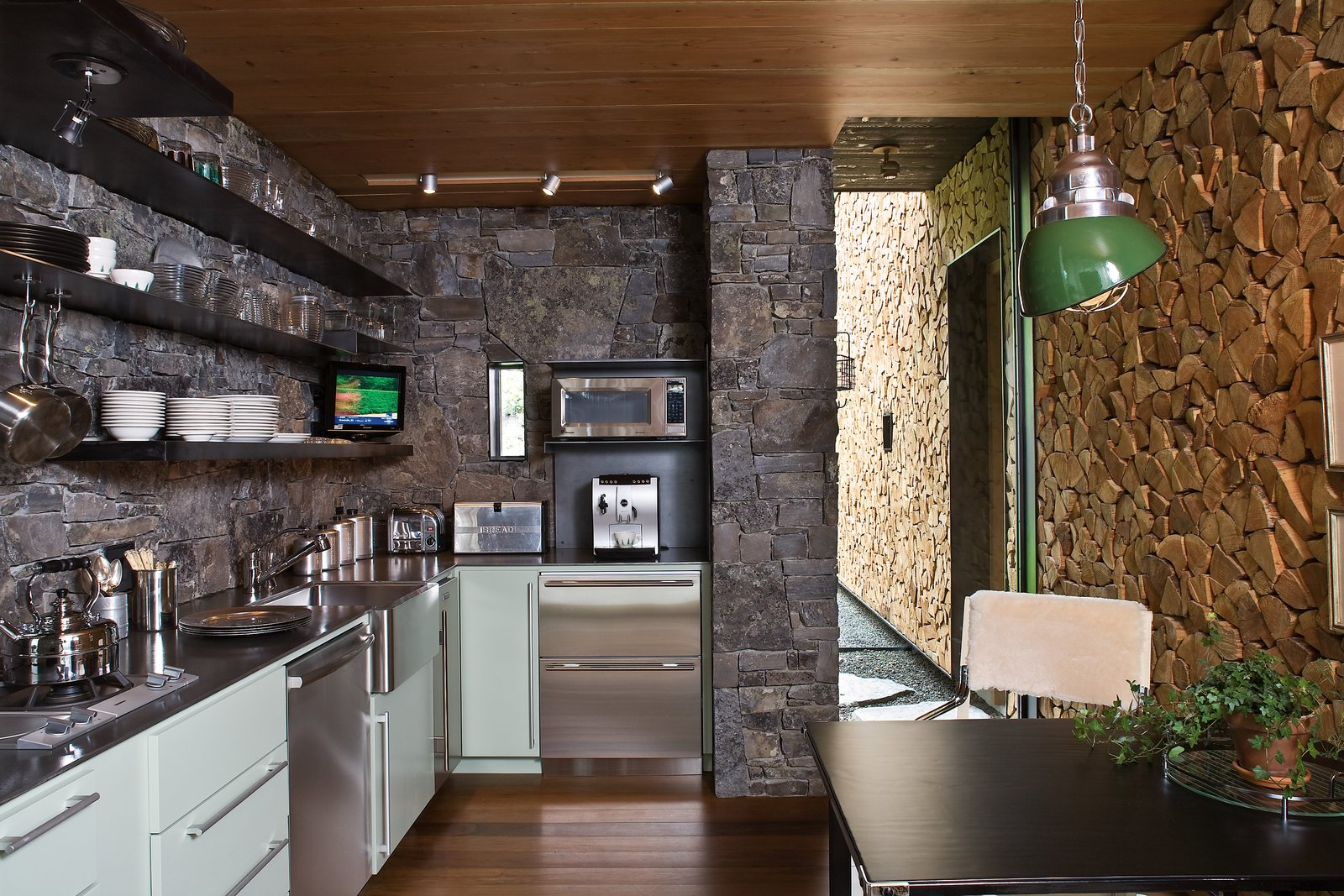 Kitchen, Track Lighting, Refrigerator, Stone Slab Backsplashe, Medium Hardwood Floor, Pendant Lighting, Open Cabinet, Microwave, Metal Counter, Colorful Cabinet, Undermount Sink, and Dishwasher Natural materials such as concrete, stone, and wood give the architecture a rugged honesty that allows it to harmonize with the pine trees and stone outcroppings outdoors.  Photo 9 of 14 in Stacked-Wood Walls Tie This Eco-Friendly Camp to the Montana Landscape