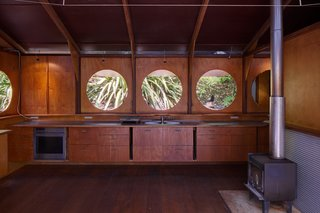 Within, light and fresh air stream through large portholes that are operable via a pulley system.
