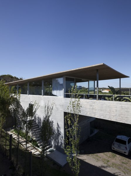 Through a winding gravel path cutting through the native vegetation, one arrives at a parking garage, which is located the below the roof's large, overhanging eaves.