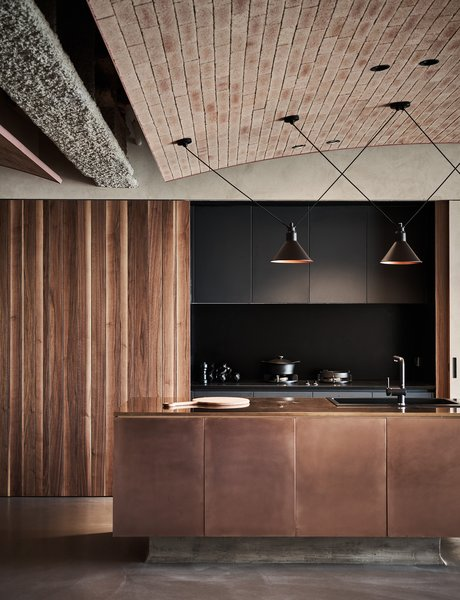 In the open kitchen, wood-paneled sliding doors conceal dark cabinetry, and together with a sleek, dark counter, and a shiny bronze-clad island with a sink, the kitchen becomes part of the overall design rather than simply an area of utility.