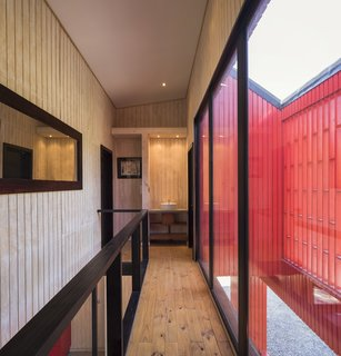 A hallway on the upper level leads to a bathroom and overlooks the front terrace.
