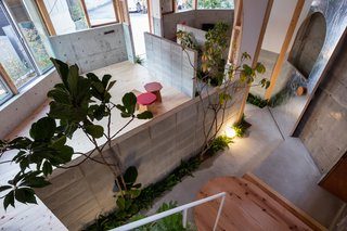 """Low walls were built along the entrance of the house to create an internal """"alley"""" that separates the two studio spaces."""