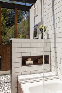 The wall without windows has a sun spotted ceramic tile dado with oak planks above it.