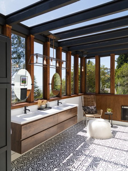 Built by Berkeley–based architect Jorgen Elmer in 1964 for renowned artist Tom Holland as a studio and home for his family, the 2,395-square-foot residence in Berkeley Hills, California, has been listed for $1,250,000 through Red Oak Realty. The updated home includes a bright and spacious remodeled master bathroom designed by Mary Cronin of The Design Shop. The new bathroom occupies what used to be an outdoor deck just off the master bedroom on the second floor. Now encased with boxed oak beams fitted with glass walls, and a glass ceiling, the bathroom is dreamy space that offers 180-degree views of the breathtaking bay.