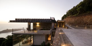 The upper volume—where the garage, kitchen, service areas, two bathrooms, and a patio are located—is a half-submerged body of stone set within the upper section of the slope.