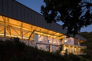 Set on the lower section of the slope, the second volume has a more modern facade, featuring concrete, steel, and glass materials.