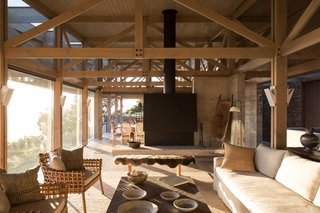 This lower volume features a series of light-filled patios. It also houses the main living areas, which are located under a wooden pavilion.