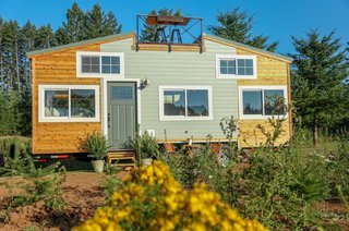 This three-story tiny house has a rooftop deck with a bar table, and large windows that bring in much light.