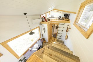 This tiny home has a fully tiled shower and a traditional staircase leading up to the master loft. An additional guest loft is accessible via a metal built-in ladder.