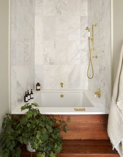 A luxurious bathtub with marble walls.