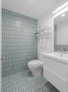 The aqua field tiles in the powder room echo the colors of the Pacific Ocean nearby.