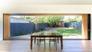 The expansive sliding glass doors in the main living area frame panoramic garden views. The deep timber extensions around the windows can now be used as bench-style seating to bring the family out into the garden, while the top eaves serve as shades to reduce heat from the strong sun exposure.