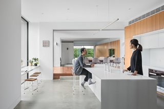 On either side of the dining area, two sets of large sliding doors connect the house to the garden.
